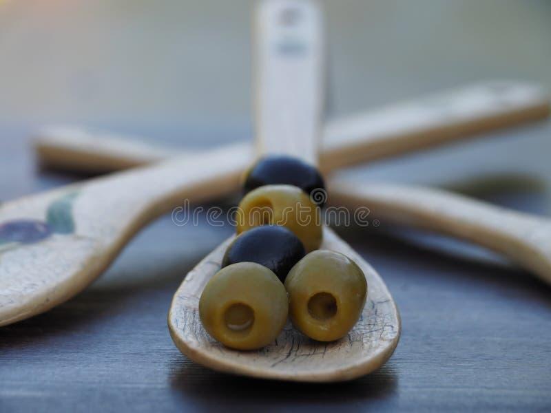 Оливки с винтажной ложкой на темном конце-вверх таблицы стоковое изображение rf