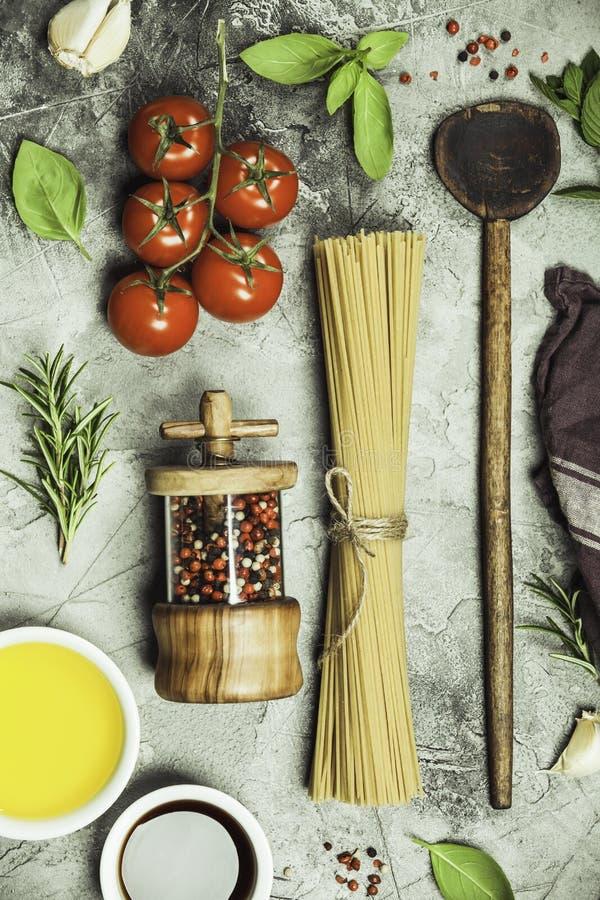 Оливковое масло, бальзамический уксус, соль, перец, травы, макаронные изделия, томаты на конкретной предпосылке стоковая фотография