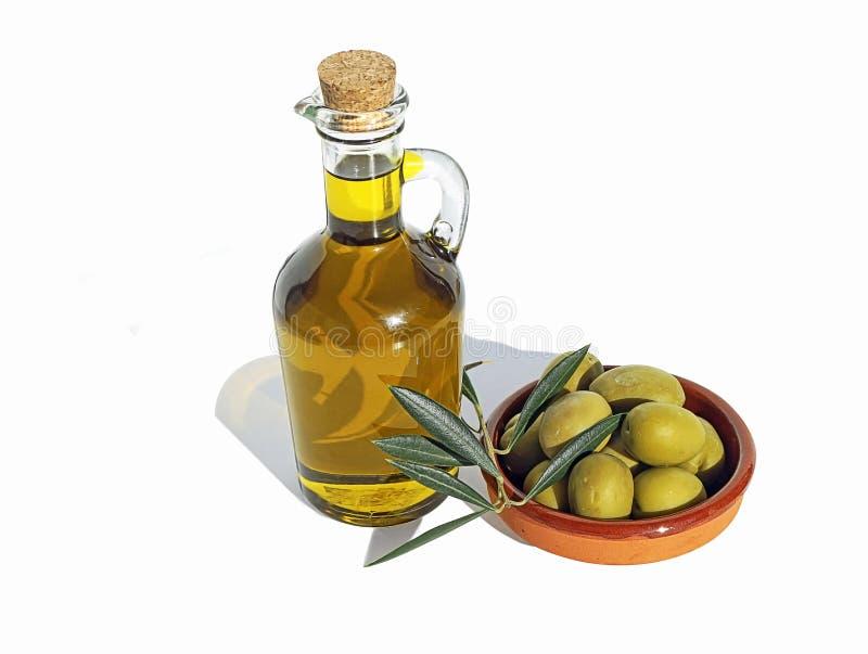 Оливковое масло в стеклянной бутылке и терракотовое блюдо с оливками стоковые фотографии rf