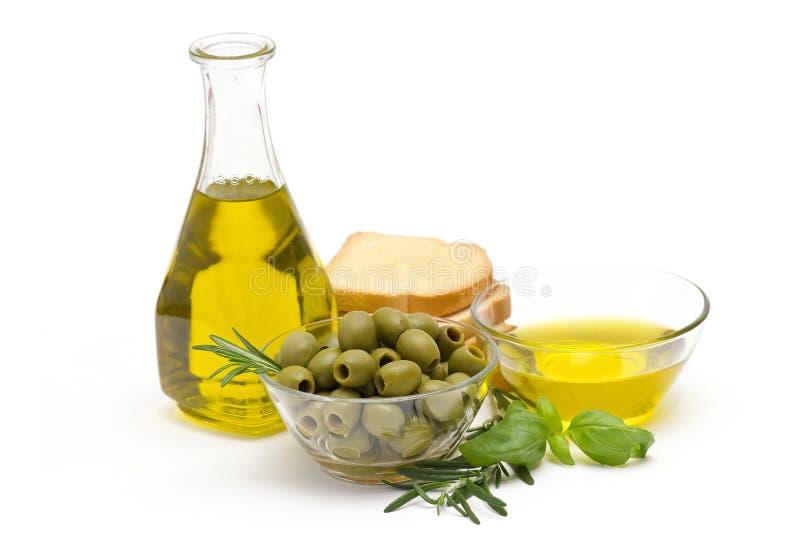Оливковое масло, зеленые оливки и хлеб стоковые фото