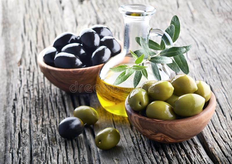 Оливковое масло и оливки на деревянной доске стоковые фото