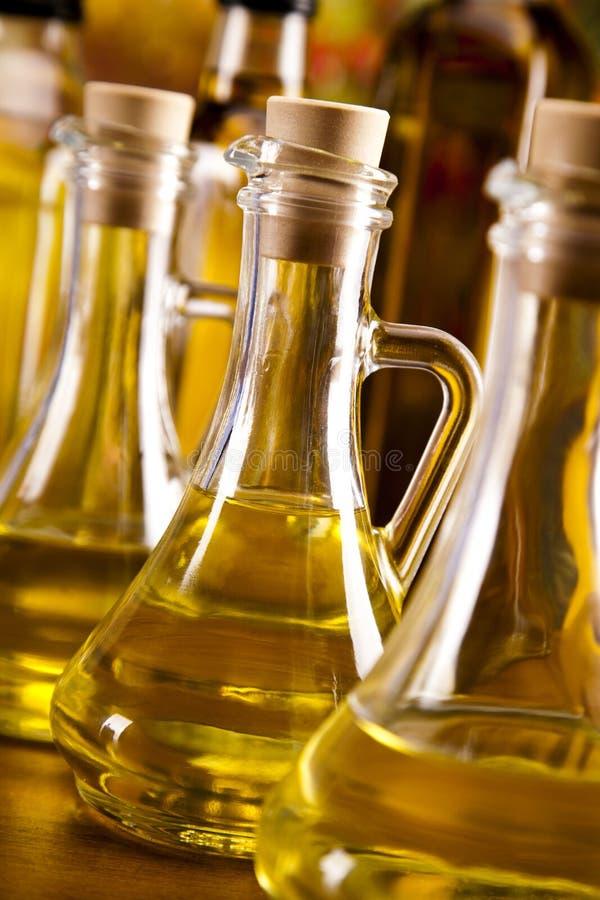 Оливковое масло разливает вертикаль по бутылкам стоковые изображения