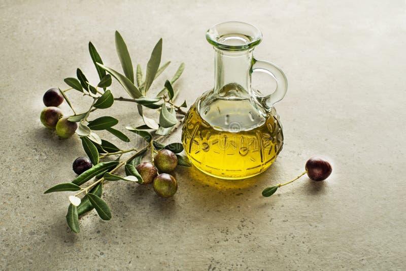 Оливковое масло с оливками и ветвью стоковые фото
