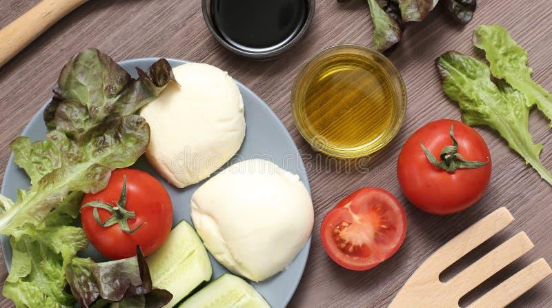 Оливковое масло томатов сыра моццареллы салата на деревянной доске Свежие продукты для диетического продукта стоковое фото