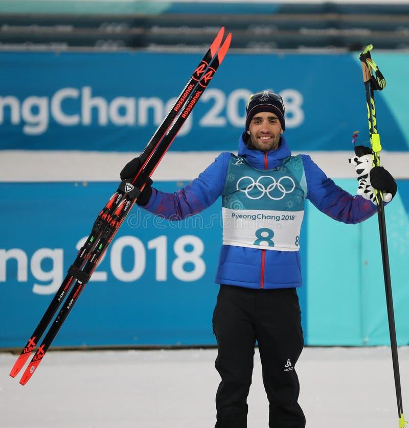 Олимпийский чемпион Мартин Fourcade Франции состязается в ` s 12 людей биатлона преследование 5km на 2018 Олимпиадах зимы стоковая фотография rf