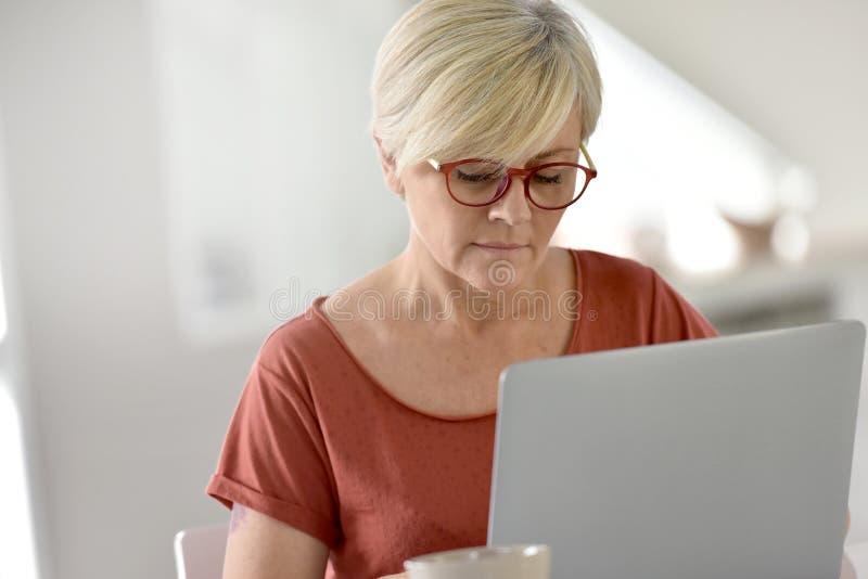 домашний старший компьтер-книжки используя женщину стоковая фотография rf