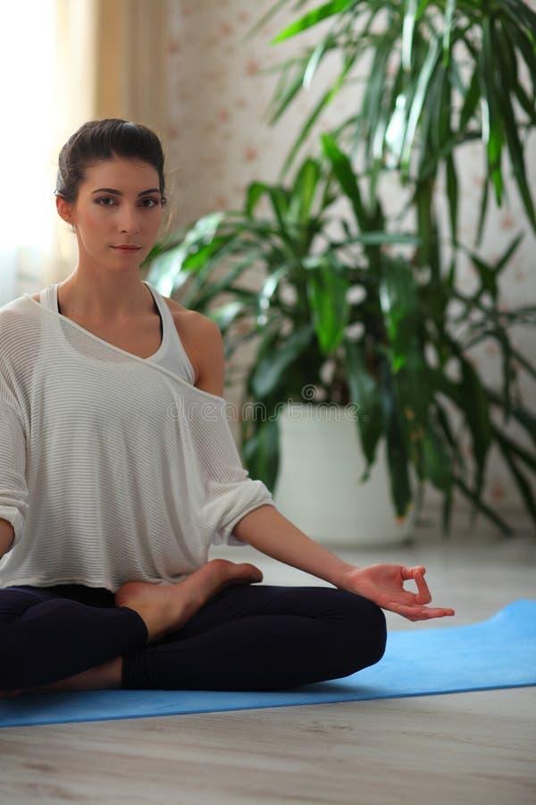 домашняя йога Держите затишье Привлекательная молодая женщина сидя на положении лотоса на поле с глазами закрыла на голубой цинов стоковое изображение