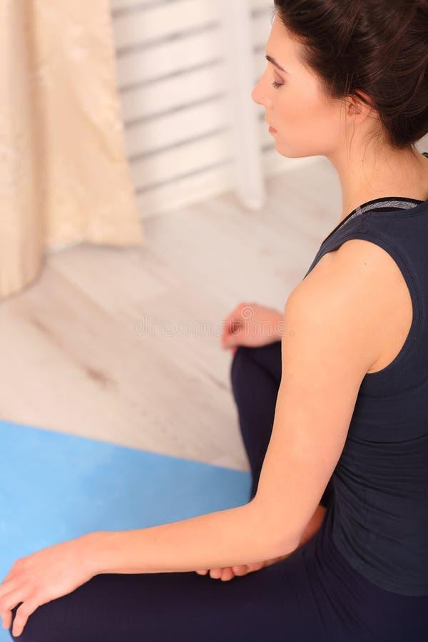 домашняя йога Держите затишье Привлекательная молодая женщина сидя на положении лотоса на поле с глазами закрыла стоковое изображение