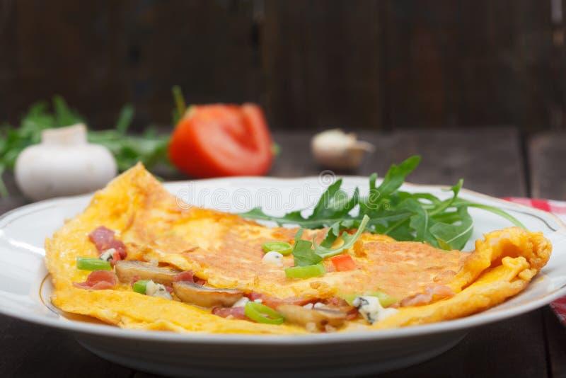 Омлет заполненный с ветчиной, сыром и грибами на плите стоковые фотографии rf