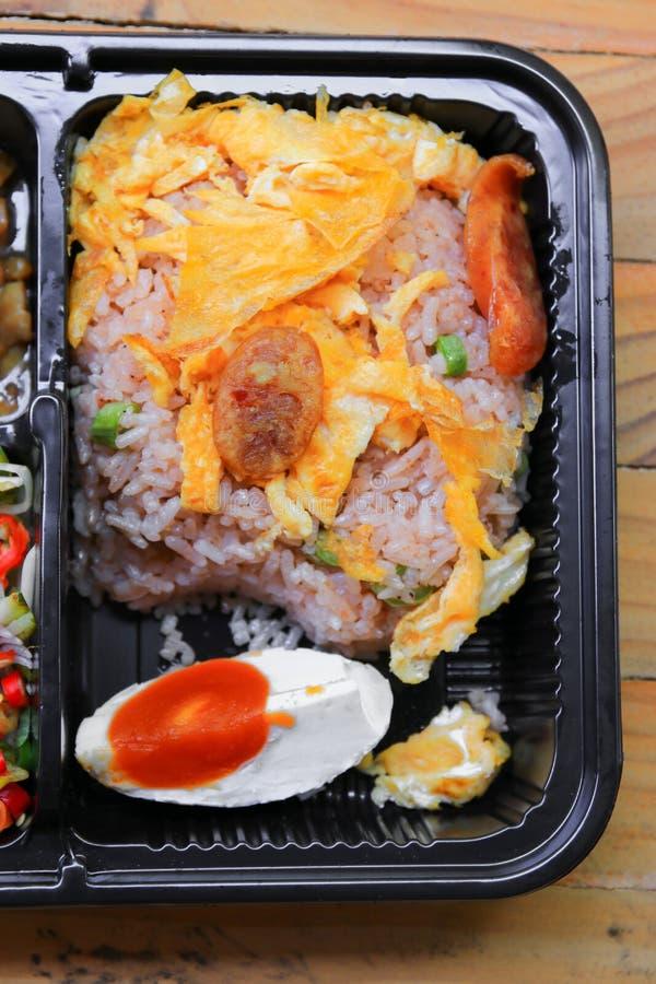 Омлет с свининой сосиски на жареных рисах закрывает вверх в еды стиля черноты коробки предпосылке таблицы тайской деревянной стоковые изображения rf