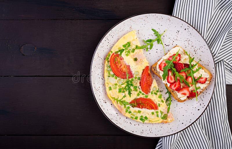 Омлет с томатами, ветчиной, зеленым луком и сэндвичем с клубникой стоковое изображение rf