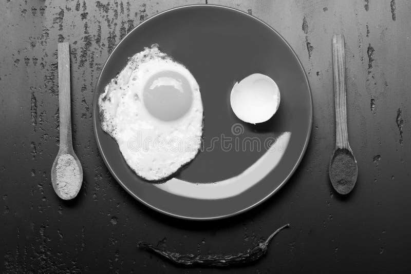 Омлет, eggshell и отражение делают усмехаясь еду стороны помещенную на красной плите на черной предпосылке, взгляд сверху стоковое фото