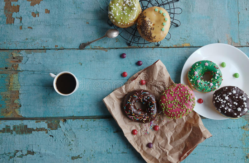 домодельные donuts на бумажном и черном кофе в белой чашке стоковое фото