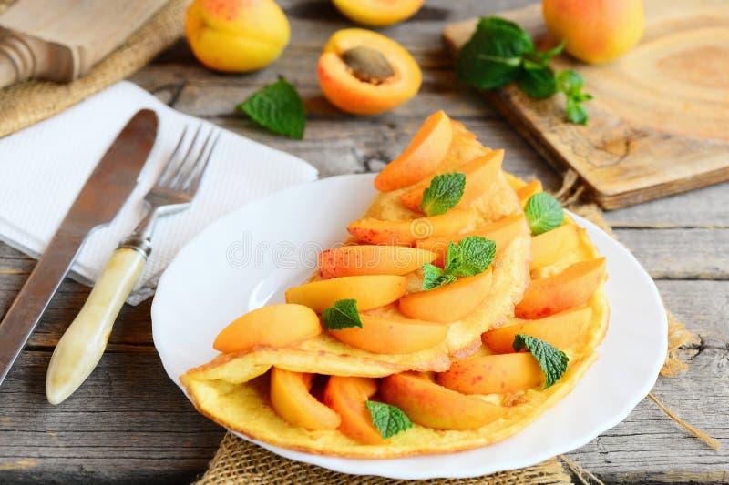 Омлет или омлет с завалкой абрикоса Омлет яичниц заполненный с свежими кусками и мятой абрикоса на белой плите сервировки стоковая фотография