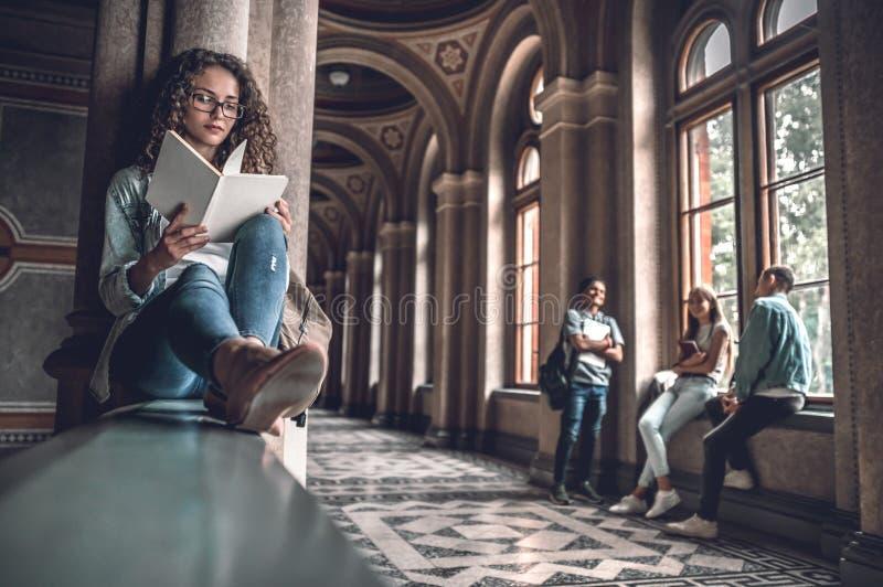Она любит прочитать Красивая студентка сидя на перилах в университете и подготавливая для экзаменов, когда ее друзья стоковая фотография
