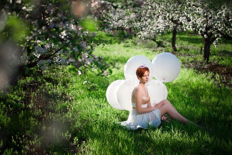 Она сидит в зеленом саде и мечтает о что-то стоковые изображения