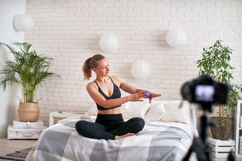 Онлайн тренер потока показывает шарик массажа тренировки метода релаксация мышц руки с шариком массажа в современном стоковое изображение