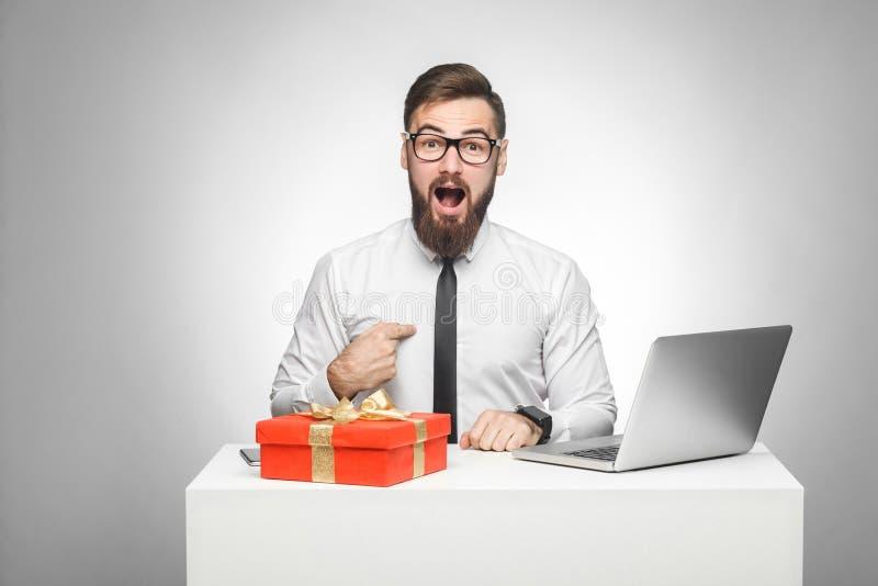 Оно для меня? Невероятный молодой человек в белой рубашке и черный галстук сидят в офисе и указывают палец на себя с сотрясенный стоковые изображения rf