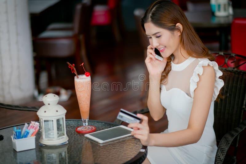 Онлайн оплата, девушка 's вручает держать кредитную карточку и usin стоковое изображение rf