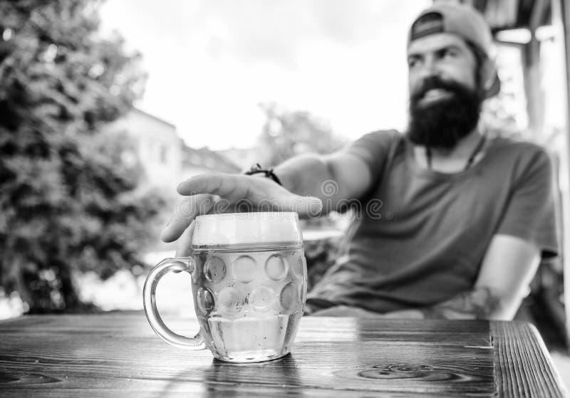Он имеет плох привычку выпивать слишком много пива Охлаженная кружка пива на таблице Пиво бородатого человека выпивая в баре Звер стоковая фотография rf
