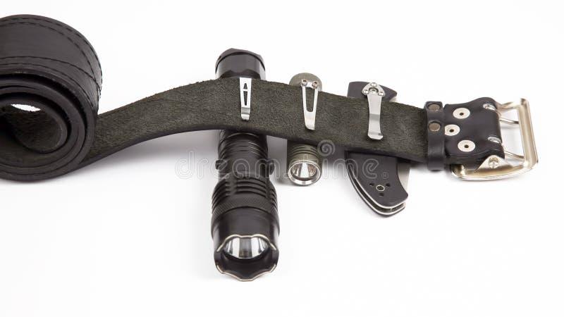 Опадающий нож, фонарик и тазер на черной кожаной ремени стоковые фото