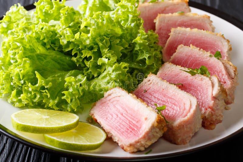Опаленный тунец ahi в обваливать в сухарях с крупным планом салата и известки на p стоковые фотографии rf