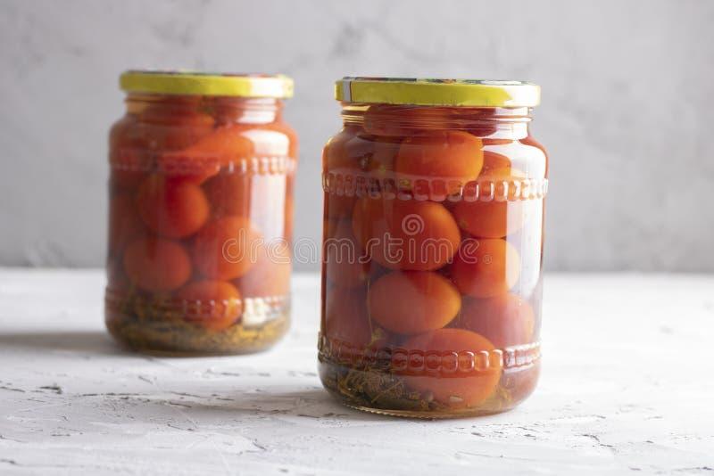 2 опарника замаринованных томатов на серой таблице, месте для текста стоковая фотография rf
