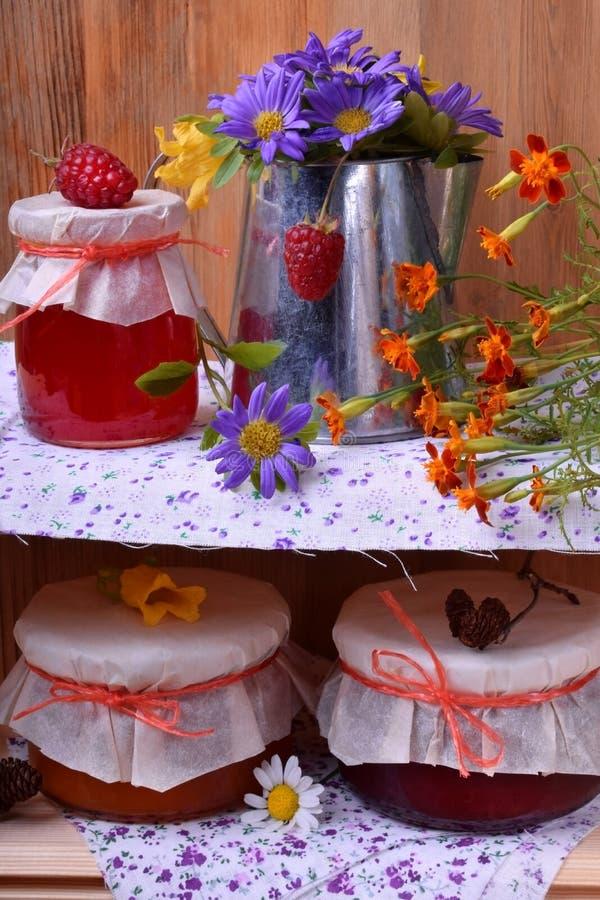 Опарникы различного варенья и металлического кувшина с цветками стоковые фото