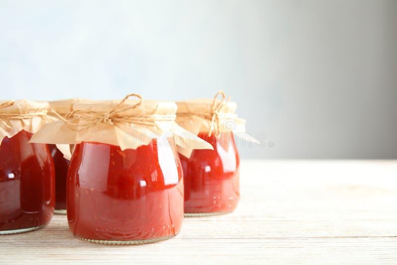 Опарникы томатного соуса на деревянном столе против серой предпосылки стоковое фото rf