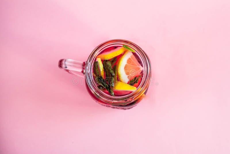 Опарник вкусного холодного лимонада на розовой предпосылке над взглядом стоковые фото