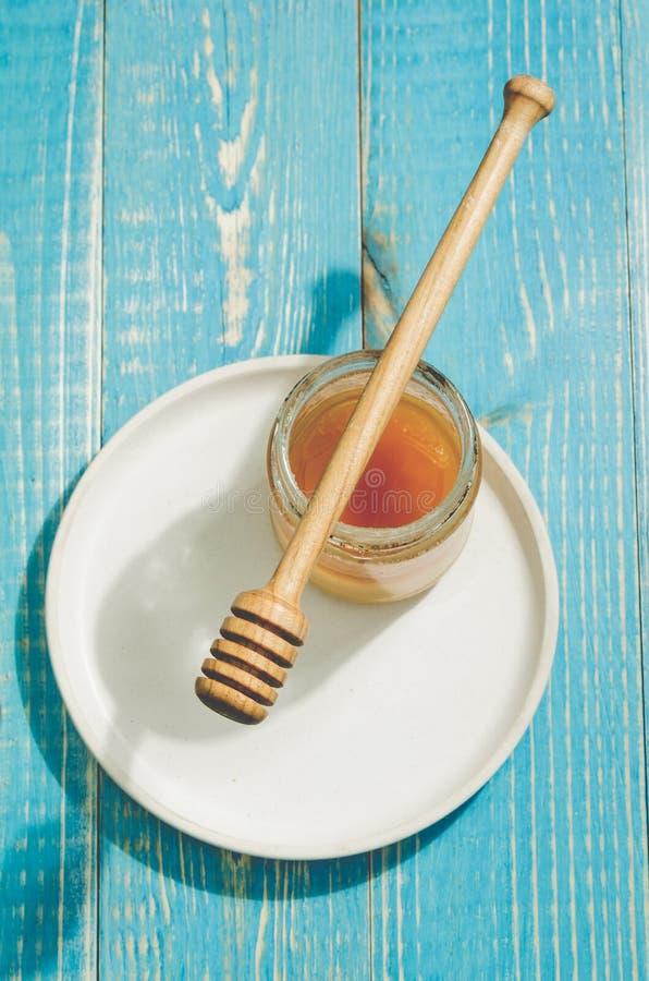 Опарник меда и ковша в белом шаре на голубой деревянной предпосылке, взгляда сверху меда стоковое изображение rf