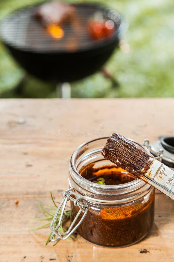 Опарник наметывать соус для мяса на BBQ стоковое фото