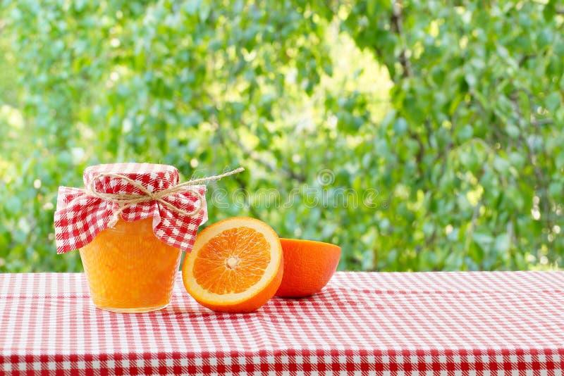 Опарник половин оранжевого варенья и апельсина на красной checkered скатерти стоковое изображение rf