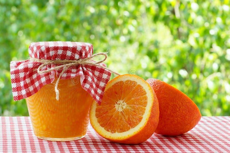 Опарник половин оранжевого варенья и апельсина на красной checkered скатерти стоковые изображения