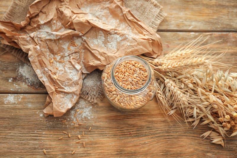 Опарник с зернами и колосками пшеницы на деревянном столе стоковое изображение rf