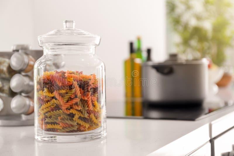 Опарник с красочными сырцовыми макаронными изделиями на таблице в кухне стоковое изображение rf