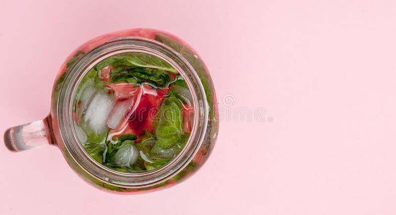 Опарник холодного свежего лимонада с частью арбуза и льда на розовой предпосылке стоковые фото
