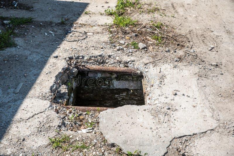 Опасная раскрытая крышка отверстия люка -лаза, опасность для людей которые идя на улицу в городе стоковые фото