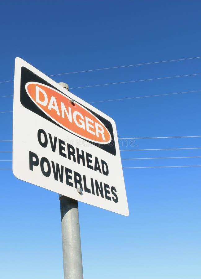 Опасность, надземный предупредительный знак powerlines с видимыми линиями электропередач стоковая фотография rf