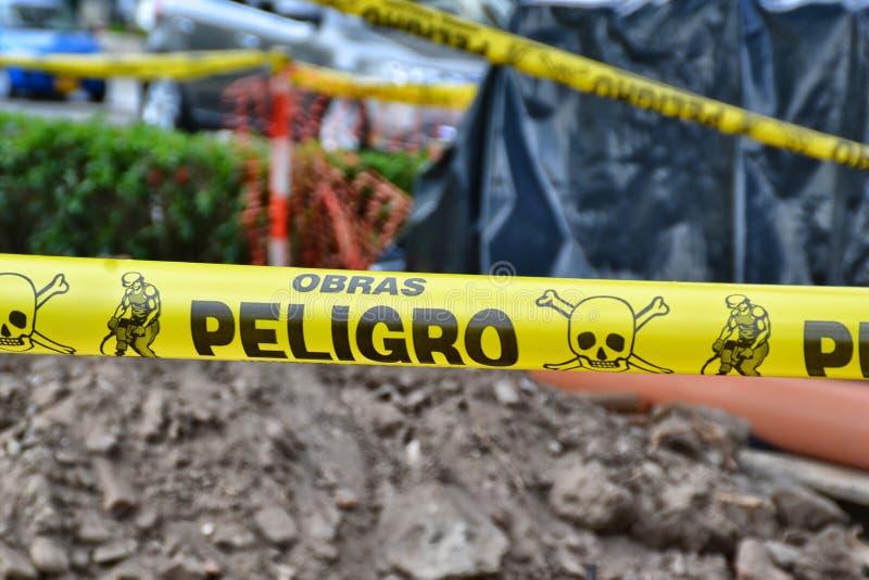 Опасность работает лента на испанском на месте производства работ стоковая фотография