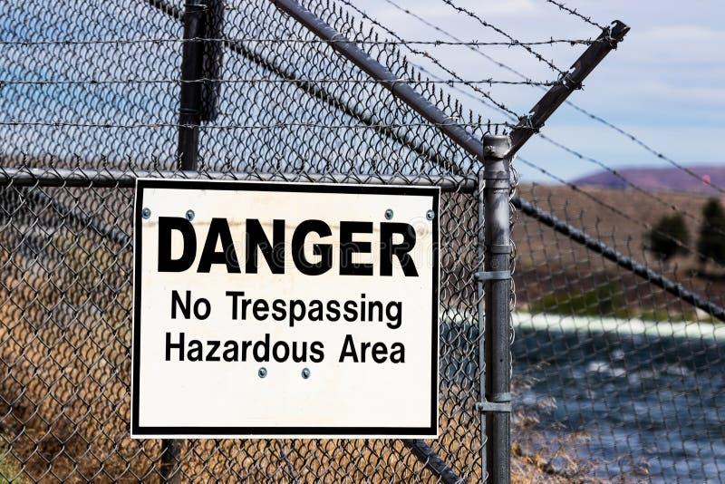 Опасный отсутствие trespassing знака опасных ares белого на загородке звена цепи колючей проволоки стоковая фотография rf