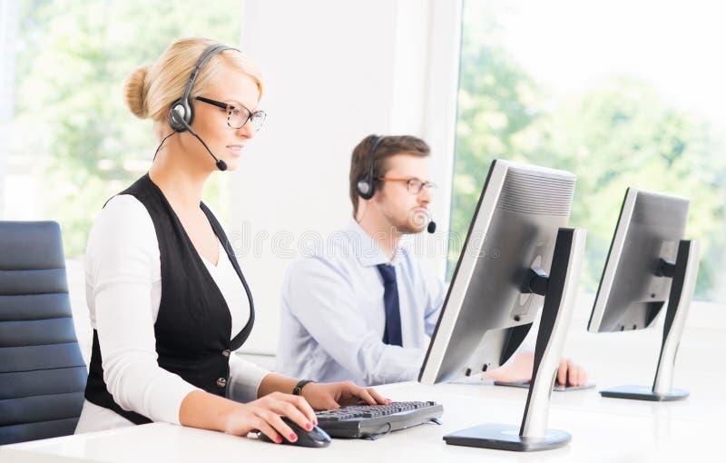 Операторы работы с клиентом в formalwear работая используя компьютеры стоковые фото