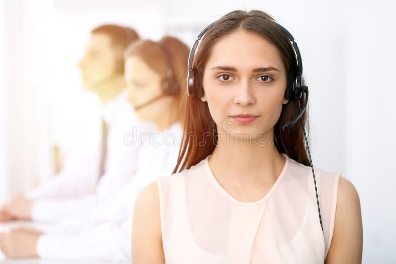 Операторы центра телефонного обслуживания Сфокусируйте на молодой жизнерадостной усмехаясь женщине в шлемофоне Концепции дела и о стоковые изображения