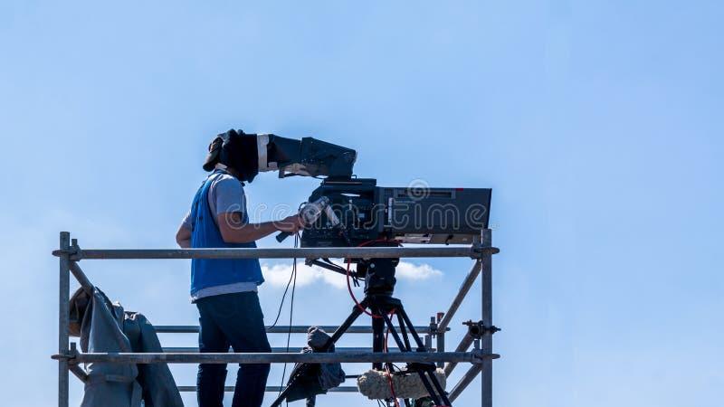 Оператор видеокамеры - человек работая и снимая на наборе с его оборудованием стоковая фотография