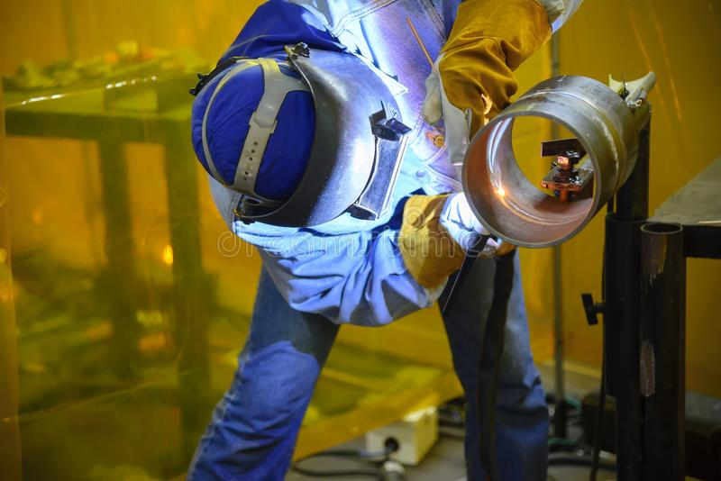 Оператор заварки искусства сваривая стальную трубу стоковые фото
