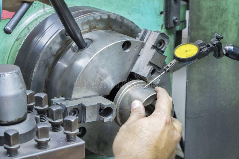 Оператор настроил поворачивая часть на ручной машине токарного станка стоковые фото
