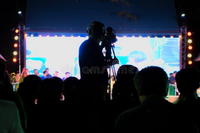 Оператор на работе, силуэте оператора оператора снимая представления в реальном маштабе времени Pong Lang на Бангкоке, Таиланде - стоковое фото