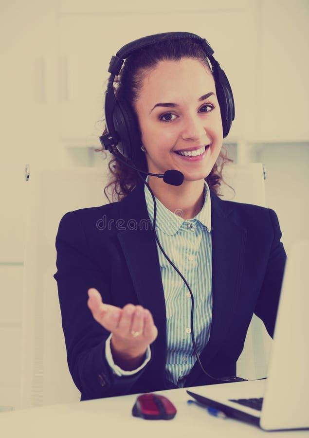 Оператор работая с клиентом шлемофоном и усмехаться стоковое фото rf