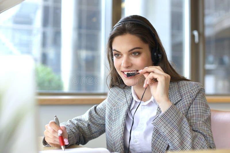 Оператор работы с клиентом женщины со шлемофоном и усмехаться стоковое фото rf