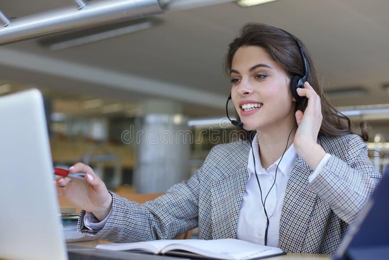 Оператор работы с клиентом женщины со шлемофоном и усмехаться стоковые изображения rf